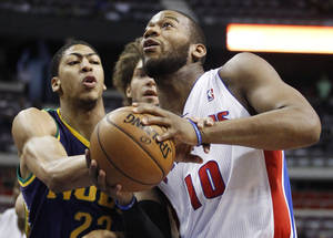 photo - Detroit Pistons center Greg Monroe (10) is fouled on the wrist by New Orleans Hornets guard Brian Roberts, left, while going to the basket in the first half of an NBA basketball game, Monday, Feb. 11, 2013, in Auburn Hills, Mich. (AP Photo/Duane Burleson)