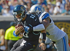 Photo -   Jacksonville Jaguars quarterback Blaine Gabbert (11) is sacked by Detroit Lions defensive end Lawrence Jackson, right, during the first half of an NFL football game, Sunday, Nov. 4, 2012, in Jacksonville, Fla. (AP Photo/Phelan M. Ebenhack)
