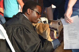 Photo - The Rev. Gerard Nsabimana, University of Central Oklahoma Wesley Foundation minister, pets a dog Sept. 9 during the Blessing of the Animals at Edmond's First United Methodist Church.  Photo by Ben Bigler, The Oklahoman