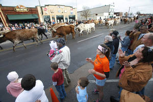 Photo - People gathered Saturday in historic Stockyards City for the annual Cowboy Christmas Parade. Above, longhorn cattle are driven down Exchange Avenue during the parade. For the story, see Page 20A. PHOTO BY PAUL HELLSTERN, THE OKLAHOMAN