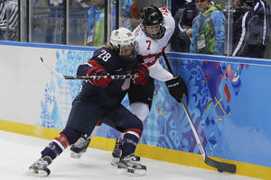 Photo - Amanda Kessel of the Untied States traps Lara Stalder of Switzerland up against the boards during the 2014 Winter Olympics women's ice hockey game at Shayba Arena, Monday, Feb. 10, 2014, in Sochi, Russia. USA defeated Switzerland 9-0. (AP Photo/Matt Slocum)