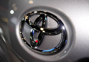 photo - FILE - This March 31, 2010 file photo shows the Toyota logo on a car at the New York International Auto Show in New York. Toyota Motor Corp. officials say the company has settled what was to be the first in a group of hundreds of pending wrongful death and injury lawsuits involving sudden, unintended acceleration by Toyota vehicles. (AP Photo/Seth Wenig, File)
