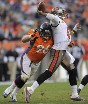 photo - Denver Broncos defensive tackle Mitch Unrein (96) hits Tampa Bay Buccaneers quarterback Josh Freeman (5) as he throws in the third quarter of an NFL football game, Sunday, Dec. 2, 2012, in Denver. (AP Photo/Jack Dempsey)