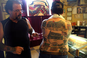 "photo - James ""The Gypsy"" George looks over tattoos on the back on Ron Jones. Photo by Tetona Dunlap"