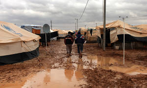 photo - Two Syrian refugees walk among tents, surrounded by water and mud, at Zaatari Syrian refugee camp, near the Syrian border in Mafraq, Jordan, Tuesday, Jan. 8, 2013. Syrian refugees in a Jordanian camp attacked aid workers with sticks and stones on Tuesday, frustrated after cold, howling winds swept away their tents and torrential rains flooded muddy streets overnight. Police said seven aid workers were injured. (AP Photo/Mohammad Hannon)