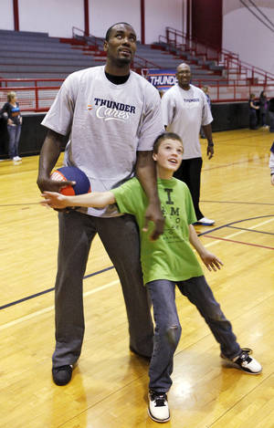Photo - Above: Sixth-grader Shaun Aberson tries to block Thunder player Serge Ibaka during a lesson Thursday at Cimarron Middle School in Edmond.