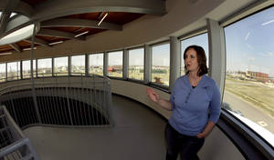 Photo - In this photo taken April, 18, 2014, museum director Stacy Barnes looks out over scattered rebuilt homes from a viewing deck at the rebuilt Big Well Museum in Greensburg, Kan. Seven years after an EF-5 tornado destroyed most of the community of 1,500, many of the town's destroyed civic buildings have been rebuilt but a rebound in population is slow in coming. (AP Photo/Charlie Riedel)
