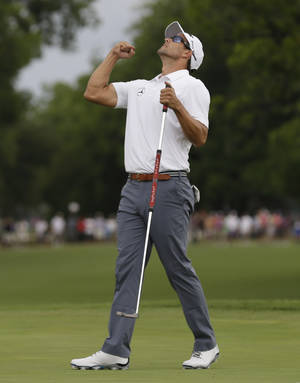 Photo - Adam Scott celebrates after sinking the winning putt on the 18th hole during the third playoff in the final round of the PGA Colonial golf tournament in Fort Worth, Texas, Sunday, May 25, 2014. (AP Photo/LM Otero)
