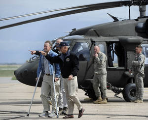 Photo - Vice President Joe Biden, center right, arrives with Gov. John Hickenlooper, left, in Greeley, Colo. after surveying the flood damage in the area, Monday, Sept. 23, 2013.  (AP Photo/The Denver Post, Kathryn Scott Osler, Pool)