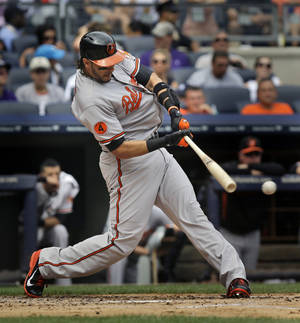 Photo - Baltimore Orioles' Michael Morse singles during the second inning of the baseball game against the New York Yankees at Yankee Stadium Sunday, Sept. 1, 2013 in New York. (AP Photo/Seth Wenig)