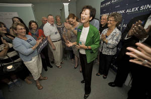 Photo - FILE - In this Nov. 23, 2013, file photo, Alex Sink, center, the state's former chief financial officer, talks with supporters and volunteers during the opening of her congressional campaign office in Clearwater, Fla. Obamacare is on the ballot in a big way in a competitive House race in Florida that offers a preview of the nationwide campaign for Congress this fall. (AP Photo/Steve Nesius, File) (AP Photo/Steve Nesius, File)