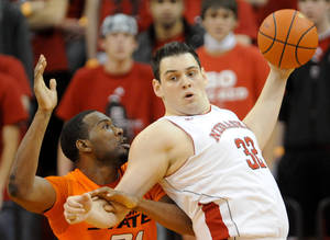 Photo - Nebraska's Andre Almeida, right, grabs a rebound in front of Oklahoma State's Matt Pilgrim. AP photo