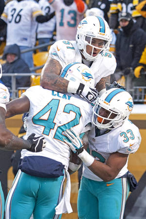 Photo - Miami Dolphins tight end Charles Clay (42) celebrates with Mike Pouncey (51) and Daniel Thomas (33) after scoring a touchdown during the second half of an NFL football game against the Pittsburgh Steelers in Pittsburgh, Sunday, Dec. 8, 2013. (AP Photo/Don Wright)