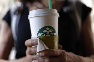 Photo -  A woman holds a coffee drink outside a Starbucks in downtown Chicago. Starbucks is raising prices on some of its drinks by 5 cents to 20 cents starting next week. AP Photo  <strong>Gene J. Puskar -  AP </strong>