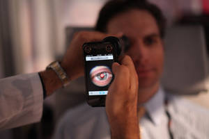 Photo - This image provided by TEDMED, shows a medical student preparing to photograph the inside of someone's eye using a special tool that taps a smartphone's camera during a recent TEDMED conference in Washington. Companies are developing a variety of miniature medical tools that hook onto smartphones to provide almost a complete physical. The hope is that this mobile medicine will help doctors care for patients in new ways, and also help people better monitor their own health. (AP Photo/TEDMED)