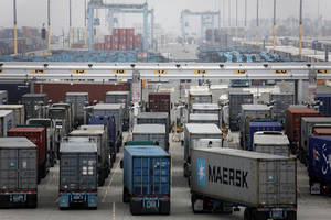 Photo - Trucks wait to be loaded at the Port of Los Angeles Wednesday,  Dec. 5, 2012 in Los Angeles. Work resumed Wednesday at the Los Angeles and Long Beach harbors after settlement of a strike that crippled the nation's busiest container port complex for more than a week.  (AP Photo/Nick Ut)