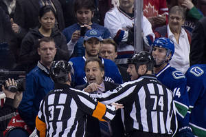 Photo - Referees get in the way of Vancouver Canucks head coach John Tortorella as he screams at the Calgary Flames bench during first period NHL hockey action at Rogers Arena in Vancouver,  British Columbia Saturday Jan. 18, 2014. (AP Photo/The Canadian Press, Jonathan Hayward)