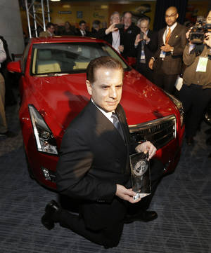 photo - Cadillac Chief Engineer David Leone kneels in front of the Cadillac ATS which was named North American Car of the Year at the North American International Auto Show in Detroit, Monday, Jan. 14, 2013. (AP Photo/Carlos Osorio)