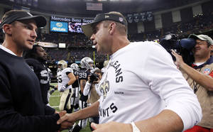 Photo - New Orleans Saints head coach Sean Payton, front right, shakes hands with Oakland Raiders head coach Dennis Allen after an NFL preseason football game at the Mercedes-Benz Superdome in New Orleans, Friday, Aug. 16, 2013. The Saints won 28-20. (AP Photo/Jonathan Bachman)