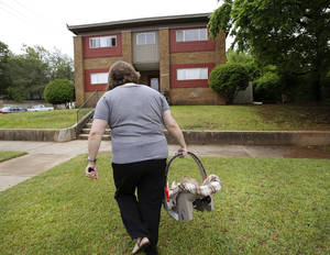 Photo - DHS child welfare specialist Katie Cooper carries an infant  to the inner city apartment of the baby's mother for an unsupervised visit on  Thursday, May, 16, 2013.  Photo  by Jim Beckel, The Oklahoman.