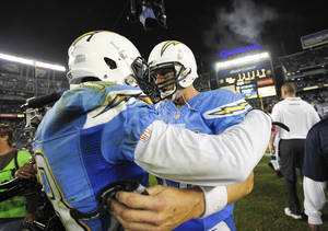 Photo - San Diego Chargers quarterback Philip Rivers, right, and  wide receiver Keenan Allen,left, celebrate after the Chargers' 19-9 victory in a NFL football game Monday, Oct. 14, 2013, in San Diego.  (AP Photo/Denis Poroy)