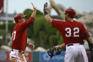 Photo - Los Angeles Angels' Mike Trout, left, celebrates with Josh Hamilton, right, after scoring on a hit by Albert Pujols during the first inning of an exhibition baseball game against the Los Angeles Dodgers in Anaheim, Calif., Saturday, March 29, 2014. (AP Photo/Kelvin Kuo)