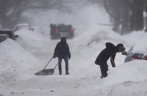 Photo - People clear snow from around their cars on a street in Montreal Sunday, Dec. 22, 2013 as a winter storm warning has been issued for the region. (AP Photo/The Canadian Press, Graham Hughes)