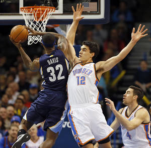 Photo - Oklahoma City's Steven Adams (12) defends Memphis' Ed Davis (32) during an NBA basketball game between the Oklahoma City Thunder and the Memphis Grizzlies at Chesapeake Energy Arena in Oklahoma City, Monday, Feb. 3, 2014. Photo by Nate Billings, The Oklahoman