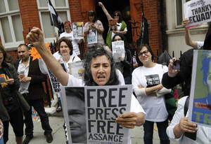 Photo - Supporters of WikiLeaks founder Julian Assange hold a vigil outside the Ecuadorian Embassy in London to mark his two years in refuge at the embassy, Thursday, June 19, 2014. Julian Assange entered the embassy in June 2012 to gain political asylum to prevent him from being extradited to Sweden, where he faces allegations of sex crimes, which he denies.(AP Photo/Sang Tan)