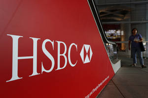 photo - FILE -- In a July 30, 2012 file photo people walk past a logo of HSBC headquarters in Hong Kong .  HSBC, the British banking giant, will pay $1.9 billion to settle a money-laundering probe by federal and state authorities in the United States, a law enforcement official said Monday Dec. 10, 2012.  (AP Photo/Vincent Yu, file)