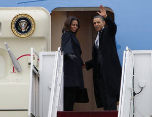 Photo - President Barack Obama, accompanied by first lady Michelle Obama, waves prior to boarding Air Force One at Andrews Air Force Base, Md., Monday, Dec. 9, 2013, before traveling to South Africa for a memorial service in honor of Nelson Mandela. ( AP Photo/Jose Luis Magana)