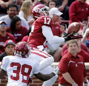 Photo - OU / UNIVERSITY OF OKLAHOMA / COLLEGE FOOTBALL: Trey Metoyer (17) catches a pass while defended by Brandon Young (38) during the annual Spring Football Game at Gaylord Family-Oklahoma Memorial Stadium in Norman, Okla., on Saturday, April 13, 2013. Photo by Steve Sisney, The Oklahoman