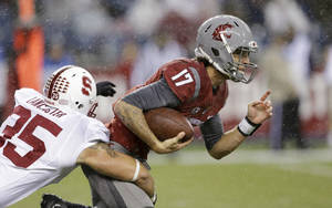 Photo - Washington State quarterback Austin Apodaca (17) keeps the ball on a run as Stanford's Jarek Lancaster in the second half of an NCAA college football game Saturday, Sept. 28, 2013, in Seattle. Stanford won 55-17. (AP Photo/Elaine Thompson)