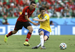 Photo - Brazil's Oscar, right, passes the ball as Mexico's Marco Fabian closes in during the group A World Cup soccer match between Brazil and Mexico at the Arena Castelao in Fortaleza, Brazil, Tuesday, June 17, 2014.  (AP Photo/Martin Mejia)