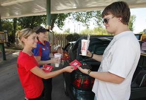 Photo - Christa Kelley with State Farm, left, and Sonic carhop Kellye Tallent surprise Dylan Swain with a free meal at the Sonic drive-in at 5625 N Western Ave.
