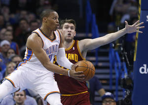 Photo - Oklahoma City Thunder guard Russell Westbrook (0) passes off in front of Cleveland Cavaliers center Spencer Hawes in the second quarter of an NBA basketball game in Oklahoma City, Wednesday, Feb. 26, 2014. (AP Photo/Sue Ogrocki)