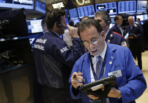 Photo - Traders work on the floor at the New York Stock Exchange in New York, Tuesday, Dec. 31, 2013.  (AP Photo/Seth Wenig)