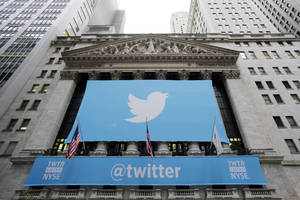 Photo - FILE - In this Thursday, Nov. 7, 2013 file photo, a banner with the Twitter logo hangs on the facade of the New York Stock Exchange in New York the day after the company went public. Stocks are down for many technology companies, including Twitter, which is down 35 percent since early March 2014. Biotechnology companies have also been hit hard. (AP Photo/Mark Lennihan, File)