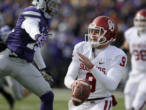 Photo - Oklahoma's Trevor Knight (9) avoids Kansas State's Randall Evans (15) during an NCAA college football game between the Oklahoma Sooners and the Kansas State University Wildcats at Bill Snyder Family Stadium in Manhattan, Kan., Saturday, Nov. 23, 2013. Oklahoma won 41-31. Photo by Bryan Terry, The Oklahoman
