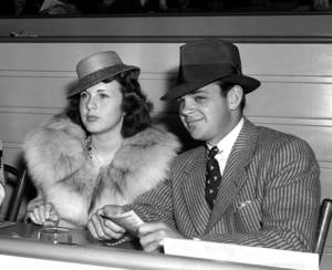 Photo - FILE - In this May 30, 1939 file photo, actress Deanna Durbin sits with Vaughn Paul in the clubhouse of Hollywood Park in Los Angeles. Paul was Durbin's first husband. Durbin, the internationally famous child star from Hollywood's Golden Age who brought her pure soprano voice and natural, girl-next-door looks to nearly 30 movies, died in April 2013. Family friend Bob Koster, whose father directed six of Durbin's films, tells The Associated Press on Wednesday May 1, 2013 that she died at age 91 in a village outside Paris in April. (AP File Photo)