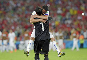 Photo - Chile's goalkeeper Claudio Bravo is embraced by Mauricio Isla after the group B World Cup soccer match between Spain and Chile at the Maracana Stadium in Rio de Janeiro, Brazil, Wednesday, June 18, 2014. Defending champion Spain was eliminated from the World Cup after losing to Chile 2-0.  (AP Photo/Bernat Armangue)