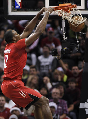 Photo - Houston Rockets forward Dwight Howard dunks during the first half of an NBA basketball game against the San Antonio Spurs on Wednesday, Dec. 25, 2013, in San Antonio. (AP Photo/Darren Abate)