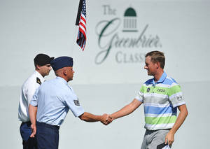 Photo - Golfer Webb Simpson, right, shakes hands with West Virginia Air National Guard TSGT Kevin Cordel during the second round of the Greenbrier Classic golf tournament at the Greenbrier Resort in White Sulphur Springs, W.Va., Friday, July 4, 2014  (AP Photo/Chris Tilley)