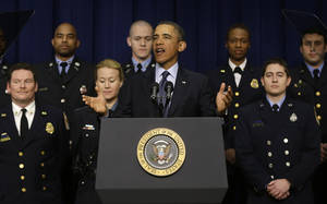 Photo - President Barack Obama, accompanied by emergency responders, a group of workers the White House says could be affected if state and local governments lose federal money as a result of budget cuts, gestures as he speaks in the South Court Auditorium in the Eisenhower Executive Office building on the White House complex in Washington, Tuesday, Feb. 19, 2013. (AP Photo/Charles Dharapak)