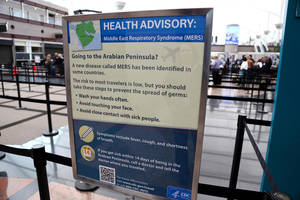 Photo - This May 14, 2014 image, provided by Denver International Airport, shows newly-erected signs warning travelers about he danger of the MERS virus, at Denver International Airport. MERS, or Middle East Respiratory Syndrome, is a respiratory illness that begins with flu-like fever and cough but can lead to shortness of breath, pneumonia and death. The airport says the signs were posted Wednesday, May 14, 2014 at all of its screening areas at the direction of the Centers for Disease Control. (AP Photo/Denver International Airport)