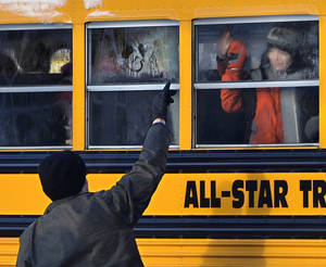photo - A man waves to a child on a bus on the first day of classes after the holiday break, in Newtown, Conn.,Wednesday, Jan. 2, 2013. Nearly three weeks after the shooting rampage at Sandy Hook Elementary School in Newtown, students and teachers from the school will return to class Thursday in the neighboring town of Monroe. (AP Photo/Jessica Hill)