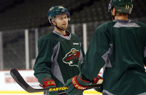 Photo - Minnesota Wild's Pierre-Marc Bouchard, left, chats with new teammate Zach Parise during NHL hockey practice, Tuesday, Jan. 15, 2013, in St. Paul, Minn. The canceled hockey games from the NHL lockout gave the Wild forward extra time to heal from his latest concussion, suffered more than a year ago. (AP Photo/Jim Mone)