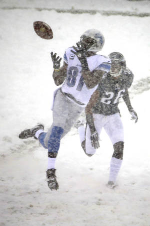 Photo - Detroit Lions' Calvin Johnson (81) catches a pass as Philadelphia Eagles' Cary Williams (26) defends during the first half of an NFL football game, Sunday, Dec. 8, 2013, in Philadelphia. (AP Photo/Matt Rourke)