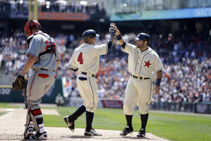 Photo - Detroit Tigers' Omar Infante (4) is greeted by teammate Alex Avila behind Atlanta Braves catcher Evan Gattis after Infante's home run during the fourth inning of an interleague baseball game in Detroit, Saturday, April 27, 2013. (AP Photo/Carlos Osorio)