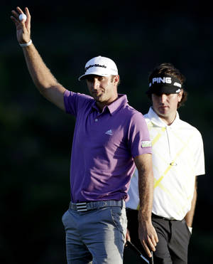 Photo - Dustin Johnson acknowledges the crowd after hitting an eagle on the 18th hole during the second round at the Tournament of Champions PGA golf tournament as Bubba Watson watches, Monday, Jan. 7, 2013, in Kapalua, Hawaii. (AP Photo/Elaine Thompson)